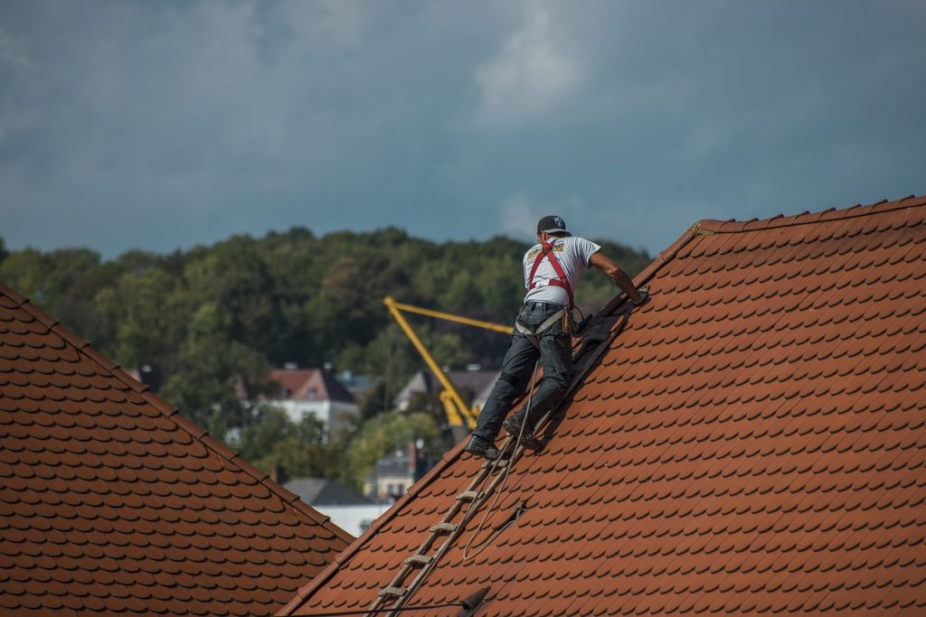 Professional Roofer on the roof in summer